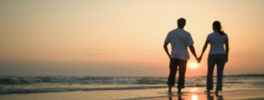A couple holding hands in front of a sunset