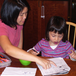 A mother helping her daughter learn to write