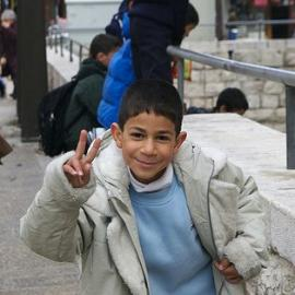 A Middle Eastern boy making a peace sign