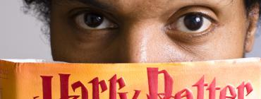 Eyes peering over a Harry Potter book