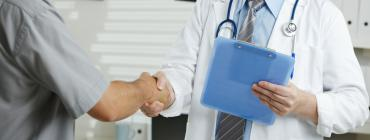 A doctor shakes hands with a patient