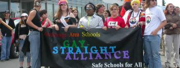 A group of gay-straight alliance students hold a banner in a pride parade