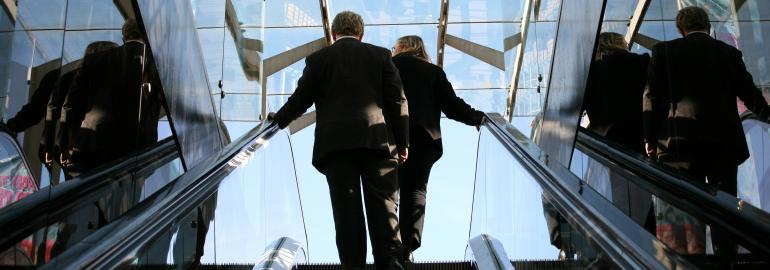 Two people in suits riding up escalator